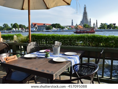 wood Dining table, view of Wat Arun, Temple of Dawn, Bangkok, central of Thailand   - stock photo