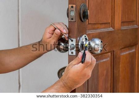 wood door and locksmith maintain silver knob - stock photo