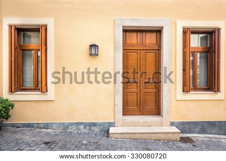 Wood door and windows with wooden shutters on peach colored wall at Santorini, Greece. - stock photo