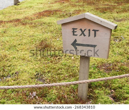 Wood exit sign with arrow pointing in a park