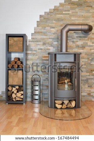 Wood fired stove with fire-wood and fire irons. With brick wall. - stock photo