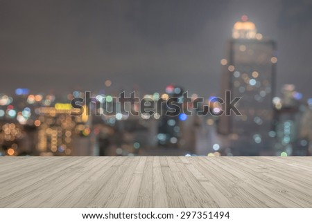 Wood floor in light red brown color tone with blurred abstract background of Bangkok night lights downtown city view with colorful bokeh and flare : Wooden table with blur background of cityscape