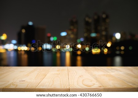 Wood floor (light and panels) with blurred abstract background of city night lights downtown city view and lake. Can be add your product on wood floor: Wooden table with blur background of cityscape.  - stock photo