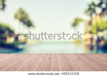 Wood floor natural wooden deck texture in light red brown color tone with blur abstract background blurry view tropical resort hotel swimming pool seaside ocean view coconut palm tree blue sky - stock photo