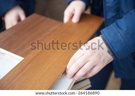 wood floor parquet shop selecting variants hands closeup - stock photo