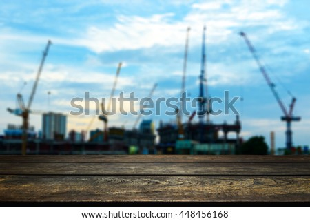 Wood floor with blurred abstract background of single tower crane and building in  construction site : Wooden table with blur background  - stock photo