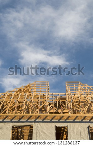 Wood framing construction on a large building with copy space in the blue sky area