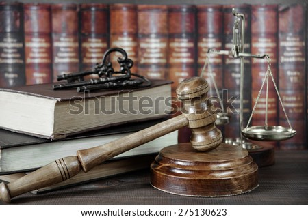 Wood gavel, soundblock, scales and stack of old books against the background of a row of antique books bound in leather