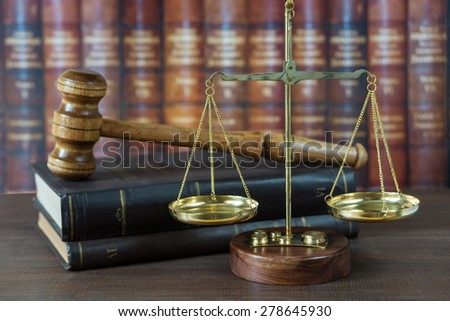Wood gavel, soundblock, scales and stack of old books against the background of a row of antique books bound in leather - stock photo