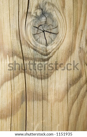Wood grain with knot and cracks in weathered post