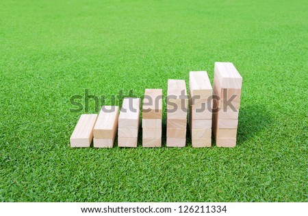 Wood Graph on the green Field for success and achievement concept.