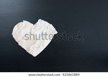wood  heart on wood table,beige lace, selective focus