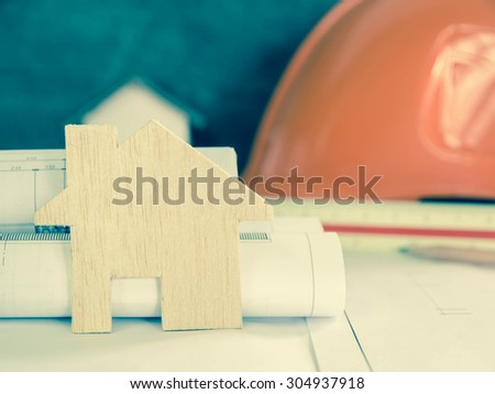wood house over blurred Safety orange hat and blueprint