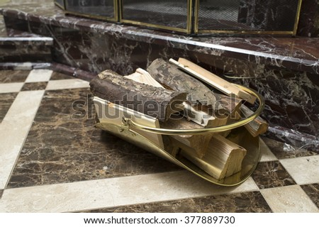 wood in the stand near the marble fireplace - stock photo
