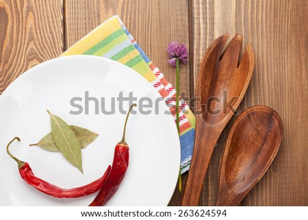 Wood kitchen utensils and spices over wooden table - stock photo