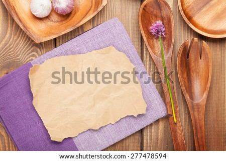 Wood kitchen utensils over wooden table background with paper for copy space - stock photo