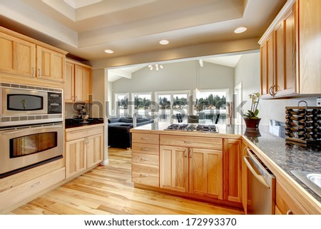 Wood kitchen with light color cabinets, hardwood floor, white ceiling and bright dining area - stock photo
