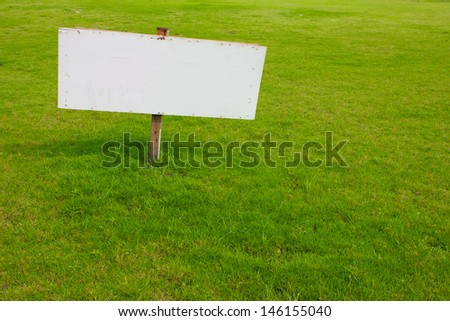 wood label sign in green grass - stock photo
