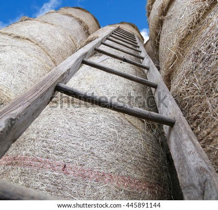 wood ladder in the barn with bales of hay and blue sky