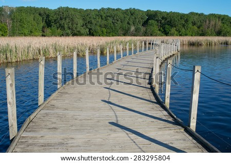 wood lake park boardwalk crossing lake and cattail marsh bordered by forest in richfield minnesota - stock photo