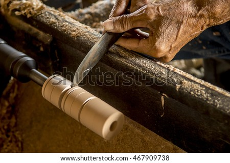 Wood lathe .The Carpenter lathing wood to make Umbrella at Bosrang Sankanpang Chiang Mai Thailand