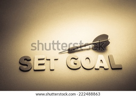 Wood letters of Set Goal word with dart