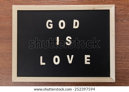 "wood letters text form bible ""GOD is LOVE"" on chalk board. - stock photo"