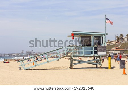 Wood lifeguard hut building protecting busy Southern California beach. American flag waving and red buoy on the structure. People enjoying the hot weather in the background.