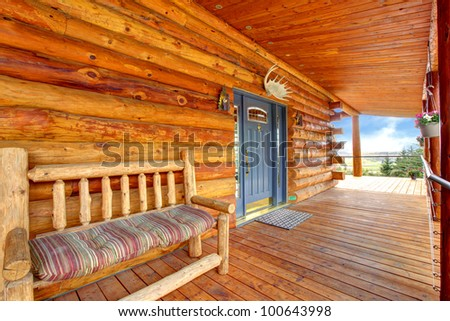 Wood log cabinet porch with entrance and bench. - stock photo