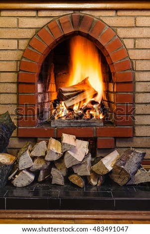 wood logs and fire in indoor brick fireplace in country cottage