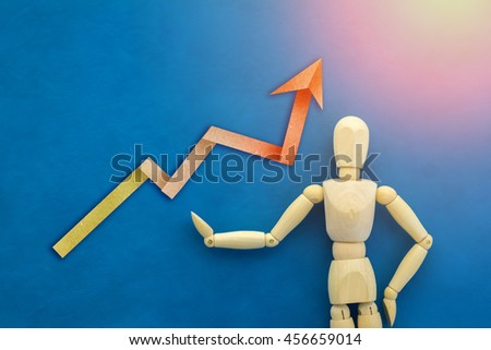 wood man figure presenting and showing business graph success on color background - stock photo