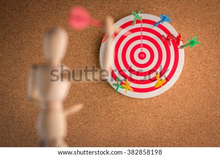 Wood Man Holding red arrow on brown with dart board focus concept - stock photo