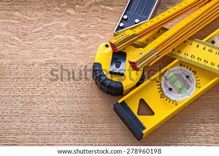 Wood oaken board with yellow objects of measurement construction concept  - stock photo