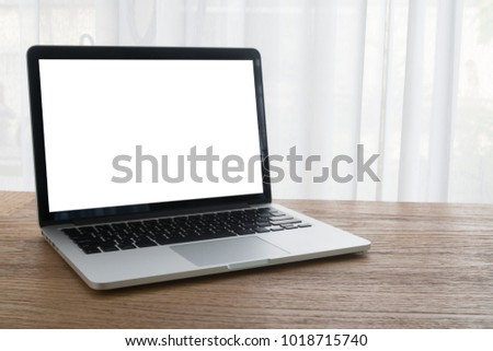 wood office table with blank screen for text  laptop, notebook on white curtain window background, view from front office table, concept of technology at home.