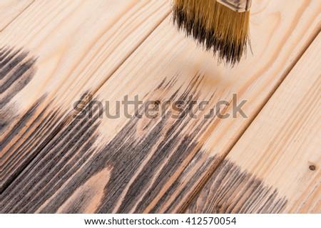 Wood painting, hand holding a brush, furniture restoration, Varnishing a wooden shelf using paintbrush, stain - stock photo