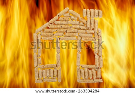 wood pellets in the shape of a house against vibrant flames - stock photo