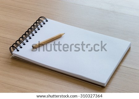 Wood Pencil Placed on a Blank Notebook - stock photo