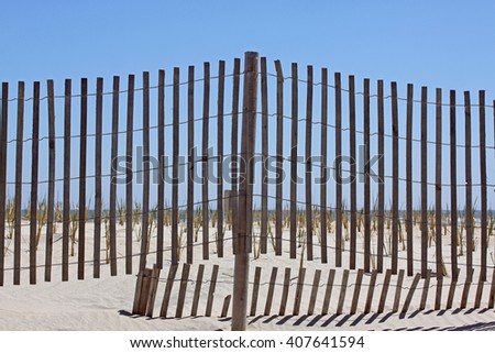 Wood picket dune fence with sand and shadows in foreground,ocean and blue sky in background.