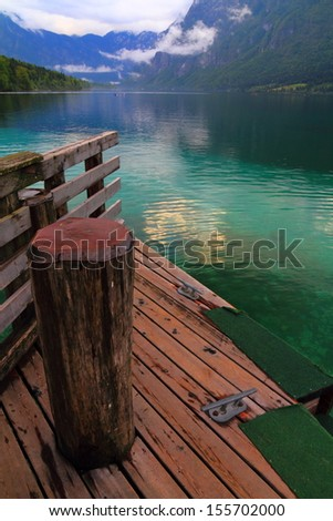 Wood pier on clear mountain lake