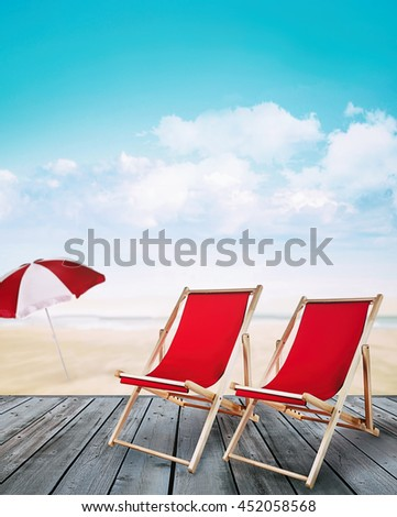 Wood pier with beach chairs and ocean in background
