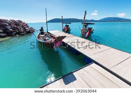 wood pier with long tail boat at khanom, nakhonsithammarat, Thailand. - stock photo