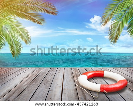 Wood pier with ocean and palm trees in background - stock photo