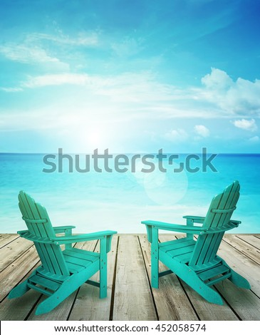 Wood pier with sun chairs and ocean in background  - stock photo