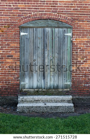 wood plank double doors at rustic brick building  - stock photo