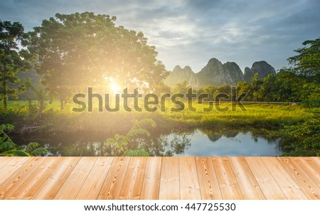 Wood plank on natural Beautiful sunset over the green large field and mountain - stock photo