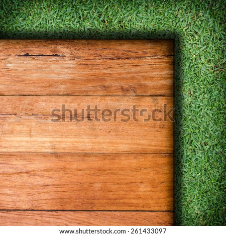 Wood plank on natural green grass field