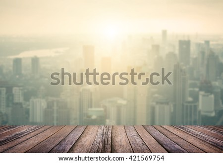 Wood plank with aerial view of cityscape at sunrise background
