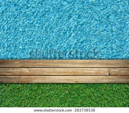 Wood plank with green grass lawn and blue pool water background - stock photo