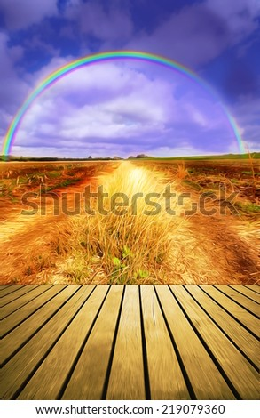 Wood planks floor background and autumn field road and rainbow. - stock photo