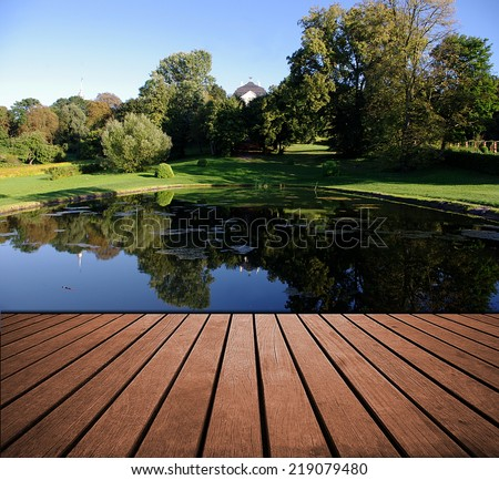 Wood planks floor background and pond or lake with garden. Summer landscape - stock photo